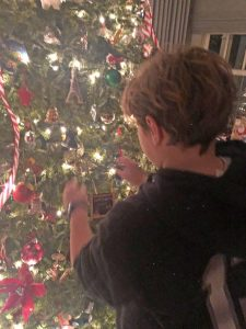 stepson hanging ornament on tree