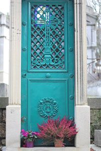 teal door to mausoleum with pink flowers outside