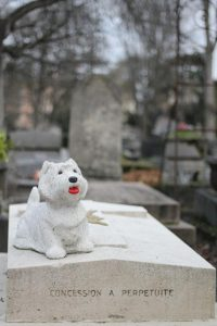 A statue of a terrier dog with red tongue on top of a grave