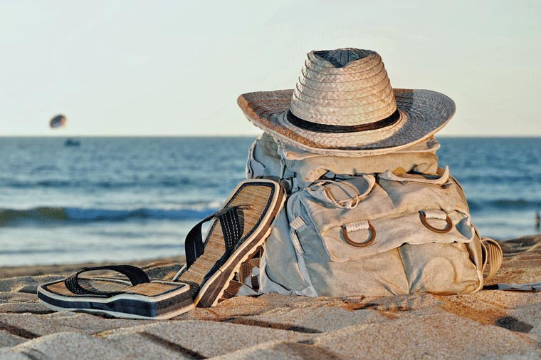 carry on bag, hat and flip flops on the beach